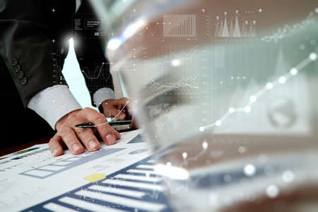 technology transaction: Close up of business man hand working with digital business layers diagram laptop computer on wooden desk as concept
