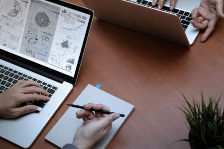 revisando documentos: vista desde arriba de dos colegas hablando de datos con el nuevo ordenador portátil moderna con el documento de estrategia de negocios y el diagrama digital como concepto Foto de archivo