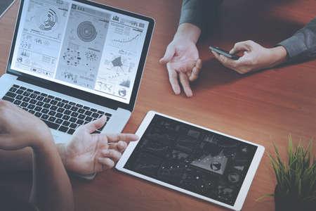 Vista dall'alto di due colleghi che parlano di dati con il nuovo computer portatile moderno e tavoletta digitale Pro con effetto di livello la strategia di business digitale sulla scrivania di legno come concetto