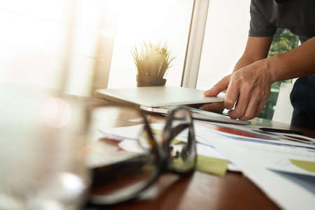companies: businessman hand working with new modern computer and business strategy documents with green plant and eyeglasses foreground on wooden desk in office