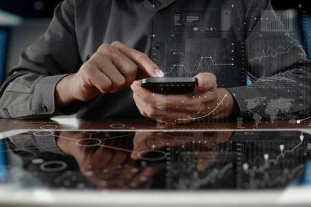 デジタル タブレット コンピューターとデジタル層ビジネス戦略と木製の机の上のソーシャル メディア ダイアグラムとスマート フォンに取り組んでいるビジネスの男の手 写真素材