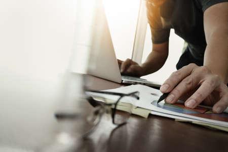 オフィスの木製の机に取り組んで新しい現代のコンピューターと水と目のガラス前面のガラスとビジネス戦略文書のビジネスマン手 写真素材