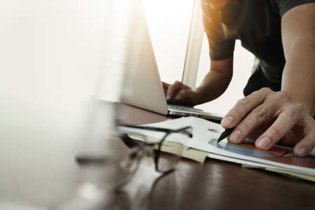 businessman hand working with new modern computer and business strategy documents with glass of water and eye glasses foreground on wooden desk in office