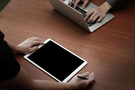 person computer: top view of two colleagues discussing data with new modern computer laptop and pro digital tablet on wooden desk as concept