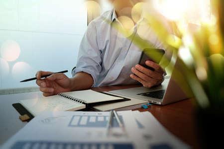 オフィスの木製の机に取り組んで新しい現代のコンピューターとビジネス戦略文書と緑色植物の前景のビジネスマン手