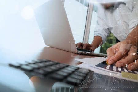 Geschäftsmann Hand mit neuen, modernen Computer und Geschäftsstrategie Dokumente digital Schicht mit grünen Pflanzen und Glas Wasser Vordergrund auf Holz-Schreibtisch im Büro arbeiten