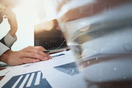 economic: business documents on office table and laptop computer and graph business with digital layer effect and man working in the background and glass of water foreground