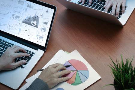 Vista dall'alto di due colleghi che parlano di dati con il nuovo computer portatile moderno con documento strategia di business e diagramma digitale come concetto