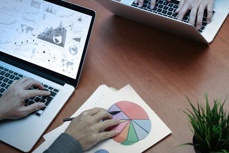 recursos financieros: vista desde arriba de dos colegas hablando de datos con el nuevo ordenador portátil moderna con el documento de estrategia de negocios y el diagrama digital como concepto Foto de archivo