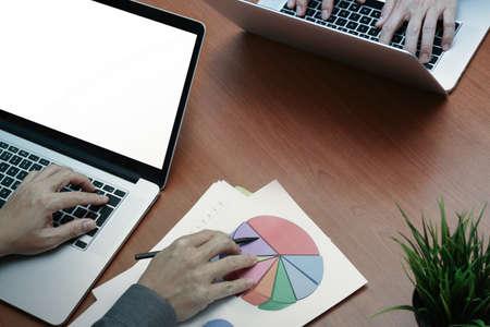 personas leyendo: vista desde arriba de dos colegas que discuten datos con una nueva pantalla en blanco moderno ordenador portátil y de negocios con el documento como concepto Foto de archivo