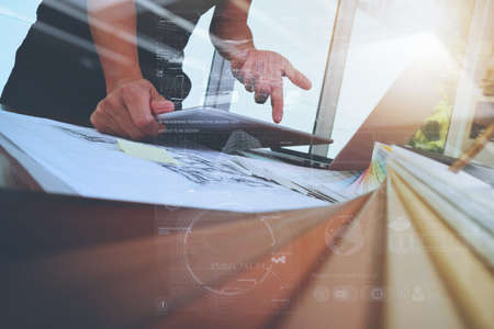 Interior designer hand working with new modern computer laptop and pro digital tablet with sample material board and digital design diagram layer on wooden desk as concept Stock Photo