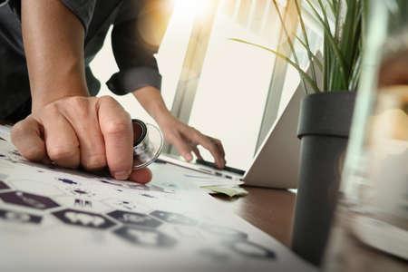 gente exitosa: médico que trabaja con el ordenador portátil en la oficina médica del área de trabajo y el diagrama de medios de red médica con un vaso de agua y el primer plano de las plantas verdes como concepto