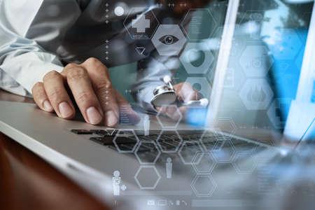 Mano della medicina lavorando a mano con computer moderni e schemi di medicina strati sulla scrivania di legno come concetto medico
