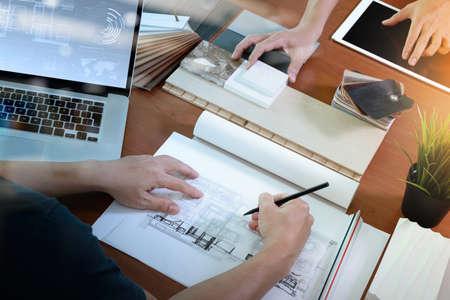 Vista dall'alto di due colleghi interior designer che parlano di dati con schermo in bianco nuovo computer portatile moderno computer e tavoletta digitale pro con materiale campione sulla scrivania in legno come concetto