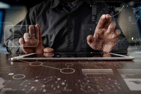 デジタル層ビジネス戦略と木製の机の上のソーシャル メディア図デジタル タブレット コンピューターに取り組んでいるビジネスの男の手