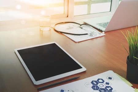 bovenaanzicht van de moderne computer en digitale pro tablet met een leeg scherm op houten bureau als medische concept