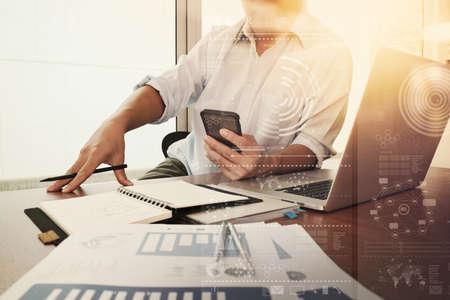 Geschäftsunterlagen auf Bürotisch mit Smartphone und Laptop-Computer und Grafik-Geschäftsdiagramm und Mann im Hintergrund arbeiten