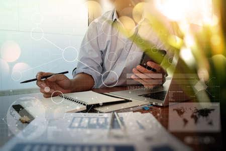 revisando documentos: negocios que trabajan con ordenador nuevo y estrategia de negocios modernos documentos digitales con capas de primer plano de la planta verde en escritorio de madera en mano oficina Foto de archivo