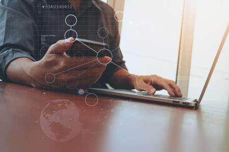 Geschäftsmann Hand arbeiten und Smartphone und Laptop mit Social-Media-Diagramm auf hölzernen Schreibtisch im Büro