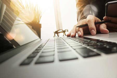 Geschäftsmann Hand mit neuen, modernen Computer und Geschäftsstrategie Dokumente digital Schichten mit grünen Pflanzen Vordergrund auf Holz-Schreibtisch im Büro arbeiten