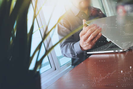 smart investing: designer hand working with laptop and business digital layer diagram with green plant foreground on wooden desk in office Stock Photo