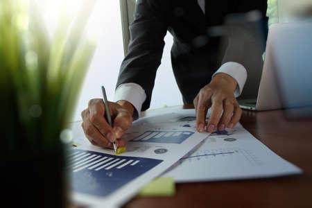 homme d'affaires travaillant main avec de nouveaux documents informatiques et de stratégie d'affaires moderne avec vert au premier plan de l'usine sur le bureau en bois dans le bureau Banque d'images