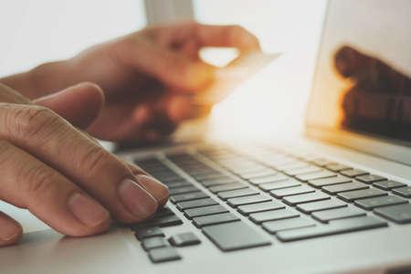 compras: las manos usando la computadora portátil y la tarjeta de crédito con el diagrama de capas de negocio digital como el concepto de compra en línea Foto de archivo