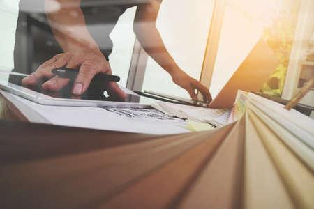 Hand Interior Designer mit neuen, modernen Laptop-Computer und Pro digitale Tablette mit Probenmaterial Platte auf Holz-Schreibtisch als Konzept arbeiten