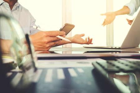 comercio: documentos de negocios en la mesa de la oficina con el teléfono inteligente y el ordenador portátil y el negocio gráfico con el diagrama de la red social y dos colegas en discusiones datos en segundo plano