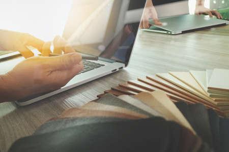 Interior designer mano a lavorare con il nuovo computer portatile moderno e tavoletta digitale Pro con scheda materiale campione e digitali strato diagramma sulla scrivania di legno come concetto Archivio Fotografico