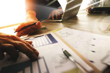 概念としての木製机の上データとビジネス ドキュメントとデジタル タブレットとコンピューターのラップトップを議論する 3 人の同僚のインテリア 写真素材