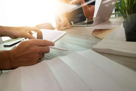 dibujo: dos colegas diseñadores de interiores en discusiones datos con la pantalla en blanco nueva computadora portátil moderna y la tableta digital profesional con material de muestra en el escritorio de madera como concepto