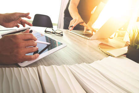 概念としての木製机の上データとサンプル素材とデジタル タブレットとコンピューターのラップトップを議論する 2 人の同僚インテリア デザイナー