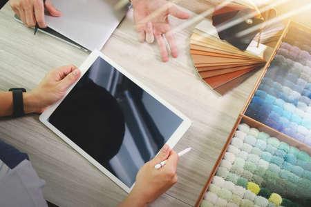 esquema: vista desde arriba de dos colegas diseñadores de interiores en discusiones con los datos de la tableta digital y portátil nuevo ordenador moderno con el material de la muestra en el escritorio de madera como concepto Foto de archivo