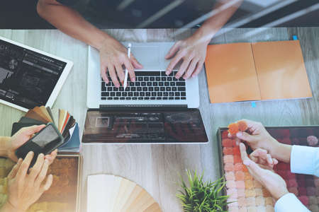 weave: top view of three colleagues interior designers discussing data with new modern computer laptop and pro digital tablet and digital design diagram with sample material on wooden desk as concept Stock Photo