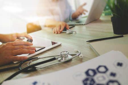 医療概念としての木製机の上現代のコンピューターと彼のチームと空白の画面とデジタル pro タブレットの使用医学医師の手の上から見る