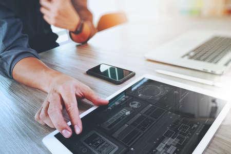 Website ontwerper die digitale tablet en computer laptop met slimme telefoon en digitale diagram op houten bureau als concept