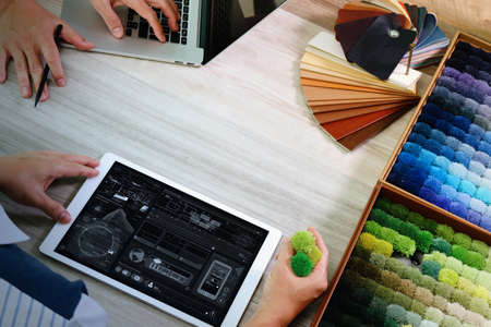 stone tablet: top view of two colleagues interior designers discussing data with digital tablet and new modern computer laptop with sample material on wooden desk as concept