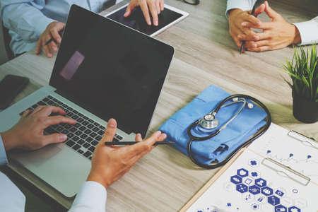 vue de dessus de médecine médecin travaillant main avec un ordinateur moderne et pro tablette numérique avec son équipe sur le bureau en bois comme concept médical Banque d'images