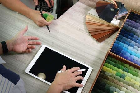 trabajando en casa: vista desde arriba de dos colegas diseñadores de interiores en discusiones con los datos de la tableta digital y portátil nuevo ordenador moderno con el material de la muestra en el escritorio de madera como concepto Foto de archivo