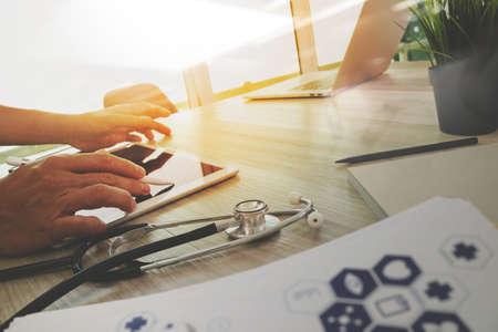 vue de dessus de la main médecin médecine de travail avec un ordinateur moderne et une tablette numérique pro avec écran blanc avec son équipe sur le bureau en bois comme concept médical Banque d'images