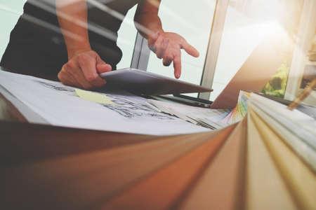 Architecte d'intérieur travaillant main avec le nouveau portable d'ordinateur moderne et tablette numérique pro avec panneau de matière échantillon sur un bureau en bois comme le concept