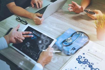 医療概念としての木製机の上現代のコンピューターとデジタル医療図と彼のチームとデジタル pro タブレット操作医学医師の手の上から見る