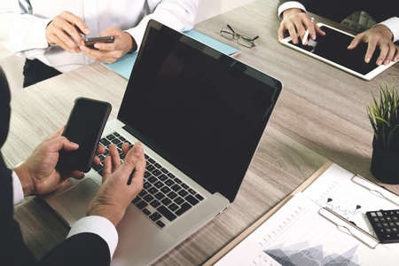 invest: business documents on office table with smart phone and blank screen laptop computer and graph business diagram and three colleagues discussing data in the background Stock Photo