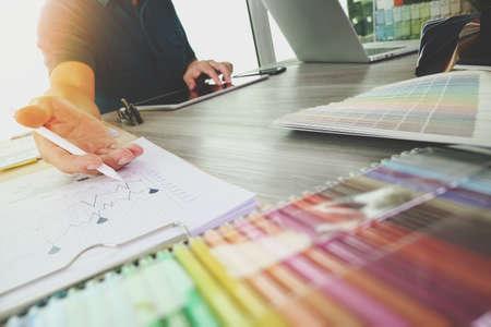 examen de la vista: dos colegas diseñador de interiores discutir datos y la tableta digital y ordenador portátil con material de muestra en el escritorio de madera como concepto