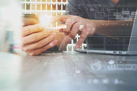 流行に敏感な手をコンセプトとして木製の机の上のデジタル デザイン ダイアグラム レイヤーをスマート フォンとラップトップ コンピューターを使