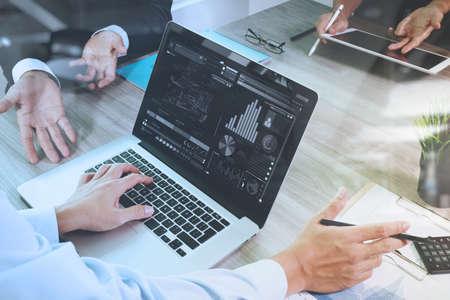 planificacion: documentos de negocios en la mesa de oficina con teléfono inteligente y el ordenador portátil y el gráfico de negocios con el diagrama de la red social y tres colegas hablando de datos en segundo plano Foto de archivo