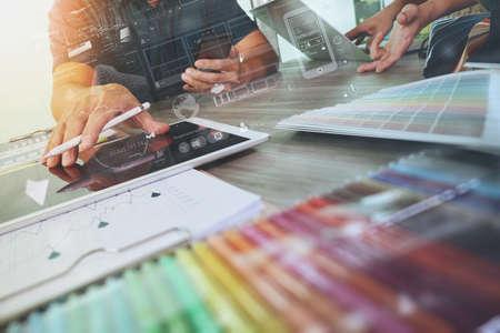 prueba de vision: dos colegas, entre diseñador de discutir los datos y la tableta digital y el ordenador portátil con el material de la muestra y el diagrama de diseño digital en el escritorio de madera como concepto