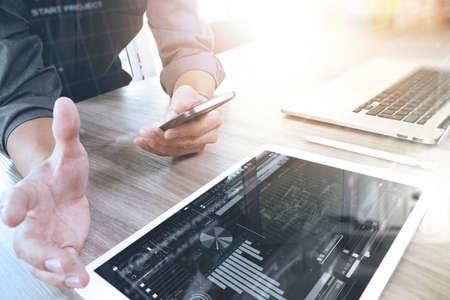 homme d'affaires travaillant avec un ordinateur numérique de la tablette et téléphone intelligent et ordinateur portable avec effet de la couche de stratégie commerciale numérique sur un bureau en bois comme le concept