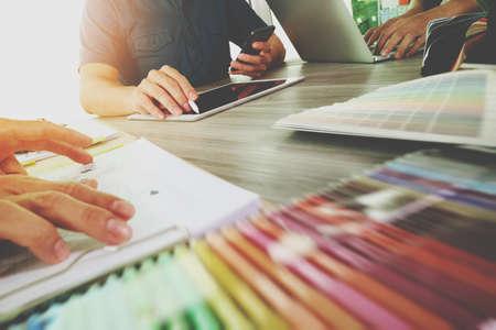 tre colleghi tra progettista discutere dati e tavoletta digitale e computer portatile con il materiale del campione sulla scrivania di legno come concetto Archivio Fotografico